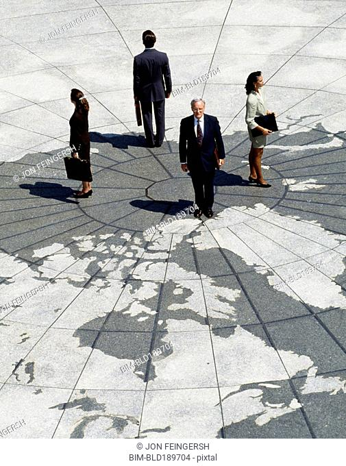 Businesspeople standing on map of globe