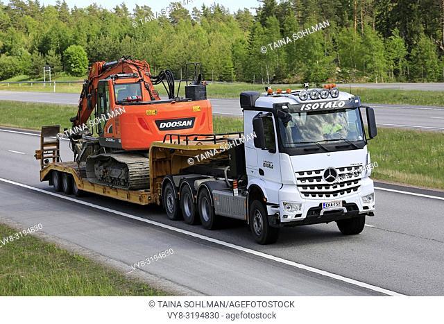 Paimio, Finland - June 1, 2018: White Mercedes-Benz Arocs semi trailer of Kuljetus Isotalo hauls Doosan DX235LCR crawler excavator on E18 freeway