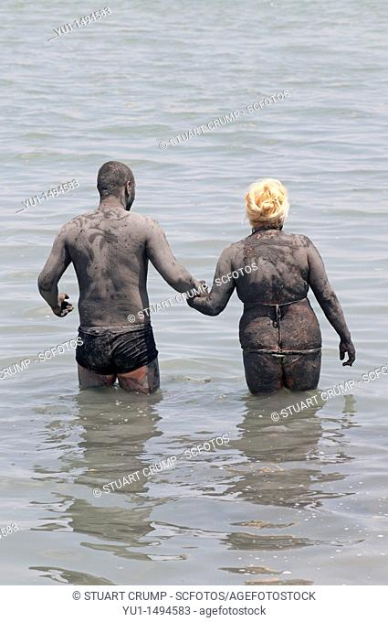 Couple cover themselves in mud from Lo Pagan beach, believed to have beneficial properties for the skin, Lo Pagan, Region of Murcia, South Eastern Spain