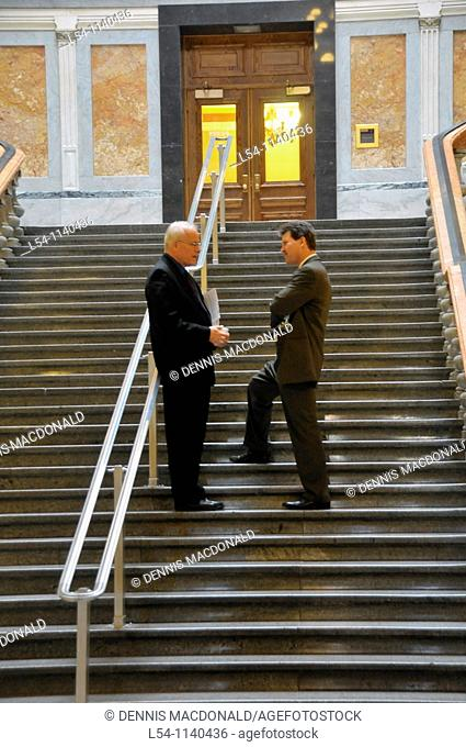 Two white males talking on steps inside state capitol Springfield Illinois
