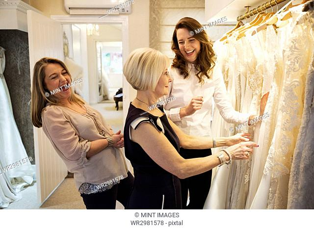Three women in a wedding dress boutique looking at a rail of white bridal gowns, with lace and decorative fabrics. A bride to be and two sales assistants...