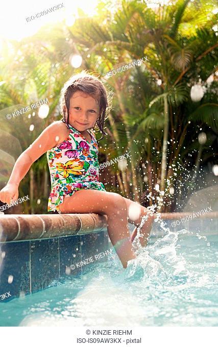 Girl wearing swimming costume sitting on sunlit poolside splashing