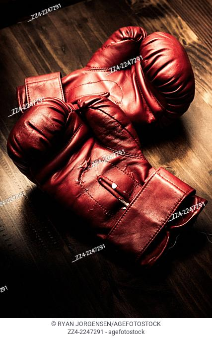 Retro style sportswear photo on a pair of red boxing gloves sitting on wooden training bench in a strength and competitive power concept