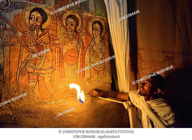 Ethiopia, Lake Tana, Gorgora, Church of Debre Sina Maryam, Deacon lighting 17th C paintings representing St Anthony, St Macarius and St Bula