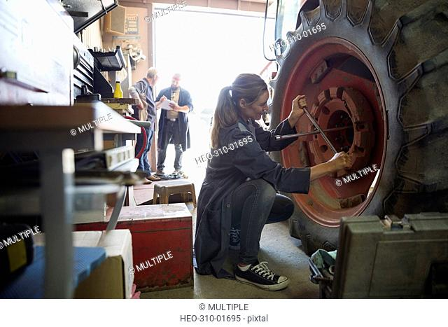 Female mechanic using lug wrench on tractor tire in workshop