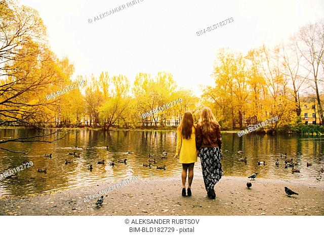 Caucasian women admiring pond in park