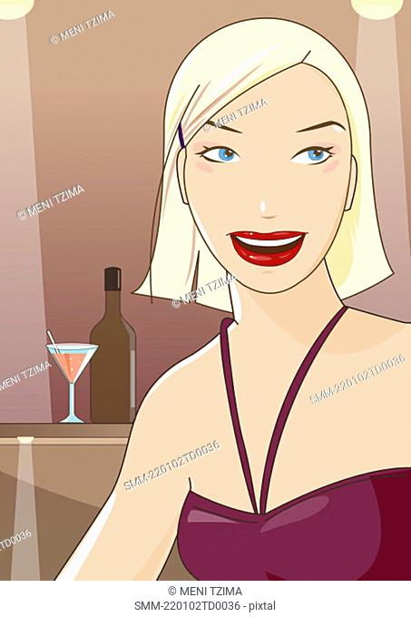 Woman smiling in a bar with her drink in the background