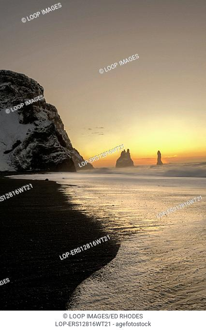 The Reynisdrangar basalt sea stacks and the Reynisfjara black sand beach at sunrise