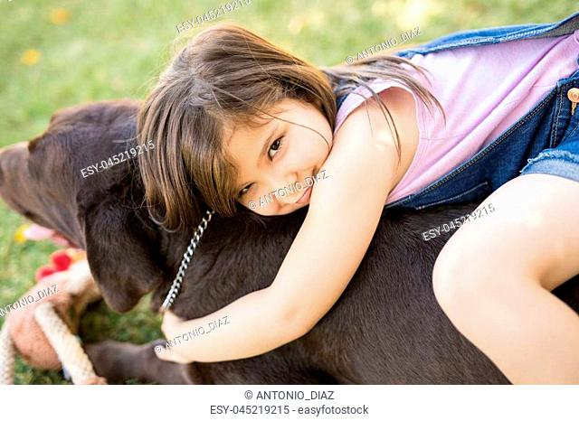 Portrait of a chubby girl sitting on pet dog embracing in garden