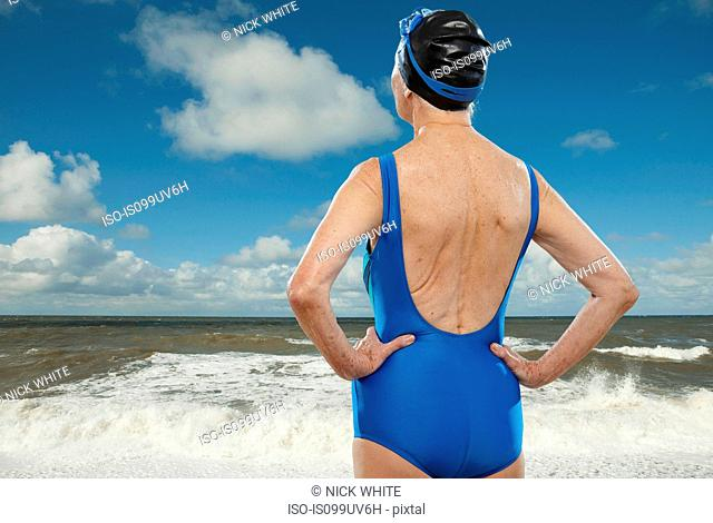 Senior woman wearing swimsuit looking towards sea