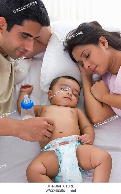 Man looking at baby sleep