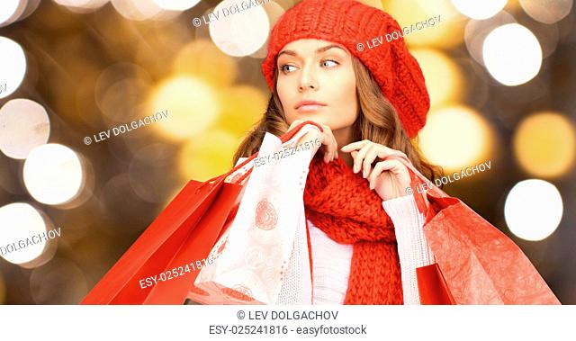 people, holidays, winter, christmas and sale concept - young woman in red woolen knitted hat and scarf holding shopping bags over lights background