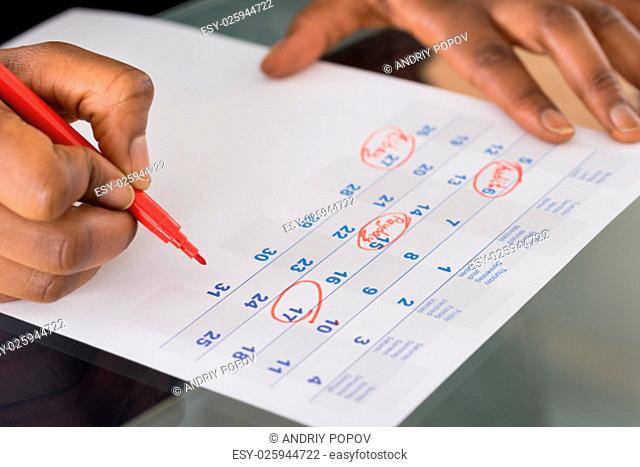 Person Circling Important Date On Calendar With Red Marking