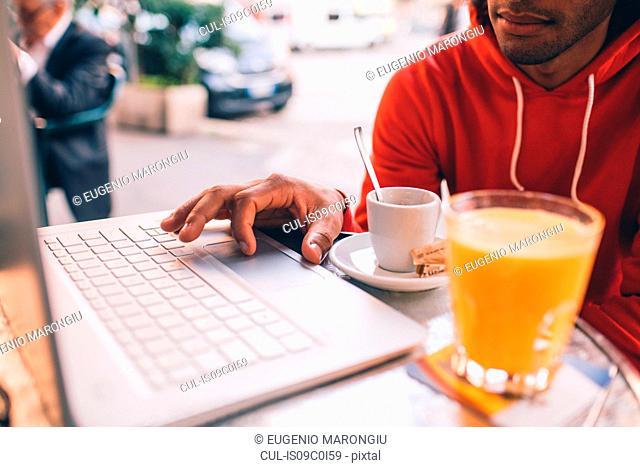 Young man using laptop at cafe