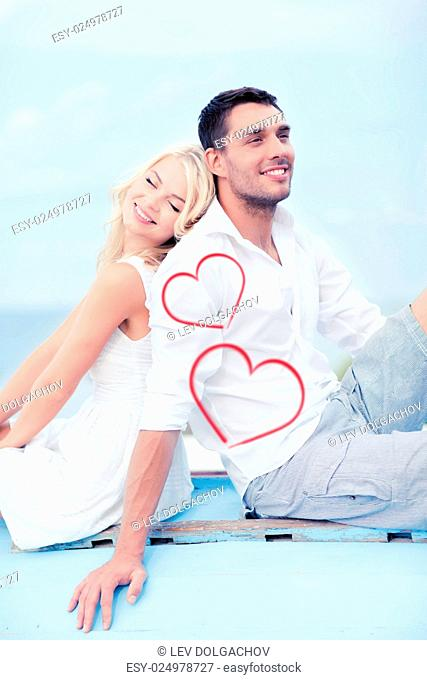 summer holidays and dating concept - couple sitting on boat at sea side