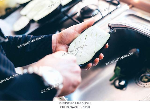 Mans hands making cuts on aubergine halves in kitchen