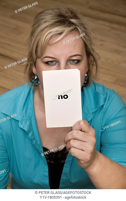 Blonde woman holding a card reading, 'no'