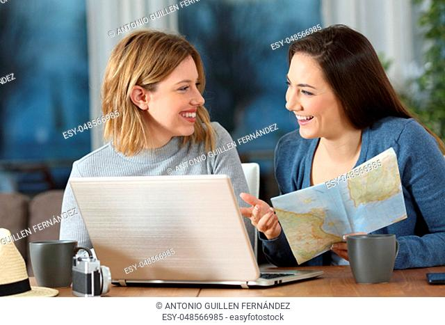 Happy friends planning travel online talking about vacation at home