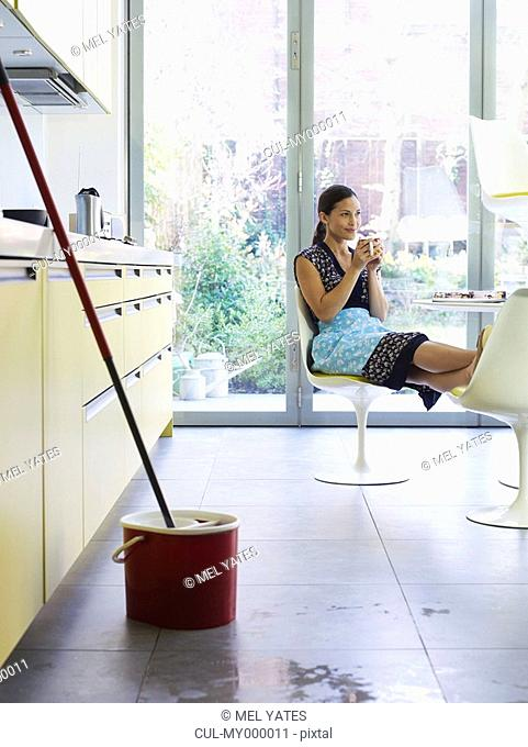 Young woman relaxing, mop in foreground