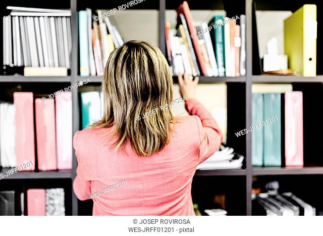 Rear view of businesswoman at bookshelf