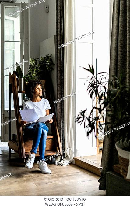 Woman sitting on steps at home with document