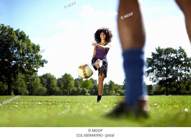 Young woman kicking soccer ball toward boyfriend in park