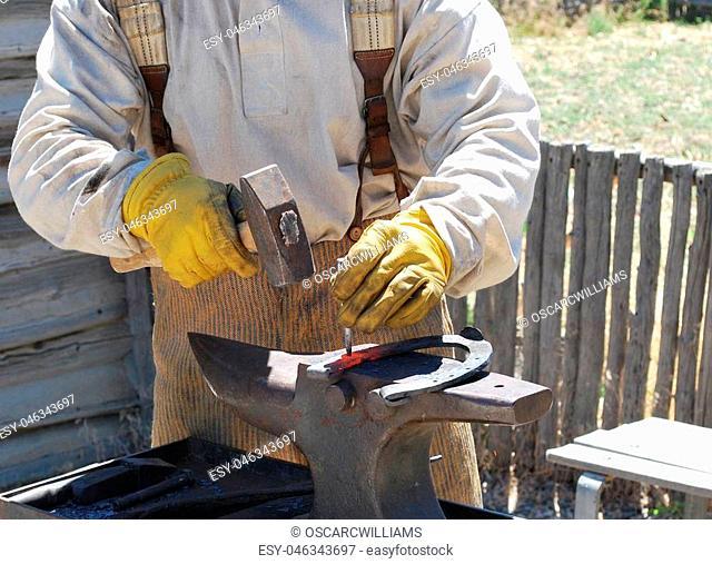 Male farrier working on a horseshoe outside