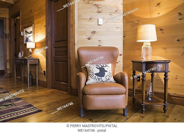 Brown leather sitting chair and wooden side table with lit clear glass lamp in boudoir on 2nd floor inside a cottage style flat log profile and timber home