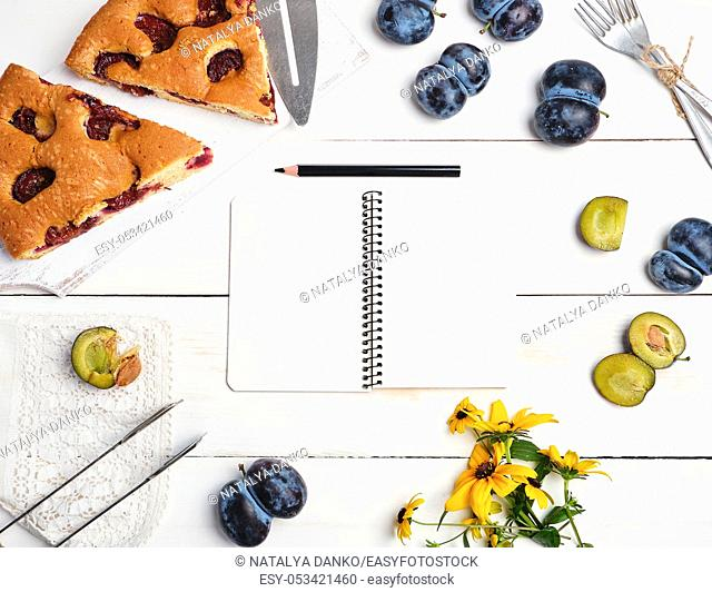 open notebook with blank white pages, baked pie with plums and fresh fruits, top viewflat lay