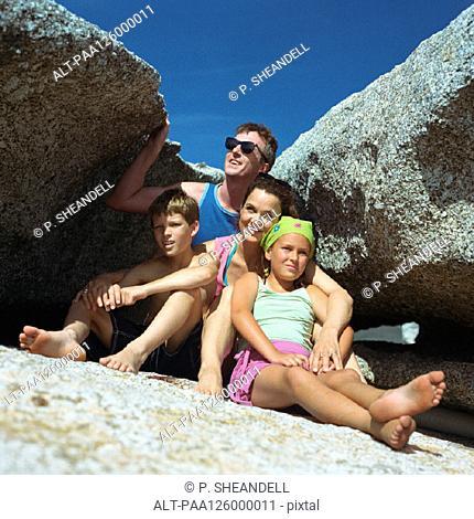 Parents and children sitting between rocks, portrait