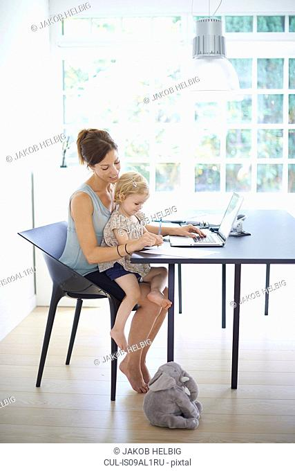 Mid adult woman and toddler daughter typing on laptop