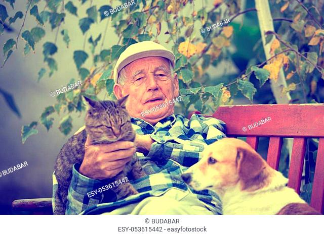 Senior man enjoying tender moments with his cat and dog, cuddling them in courtyard