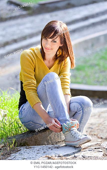 Attractive young woman is adjusting her sneakers in the park, smiling