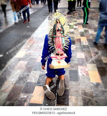 A person walking in his knees carries a sculpture of the Virgin of Guadalupe during the anual pilgrimage to Our Lady of Guadalupe Basilica in Mexico City