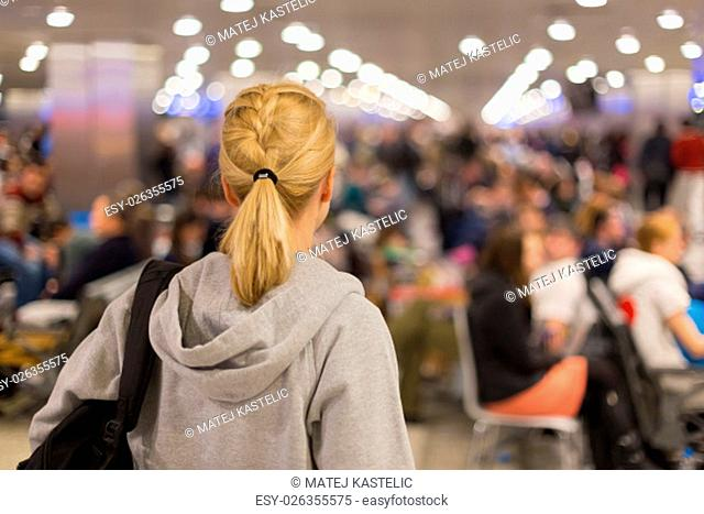 Young blond caucsian woman waiting on airport terminal full of passenegers waiting to depart