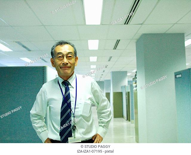 Portrait of a senior man standing in the corridor of an office