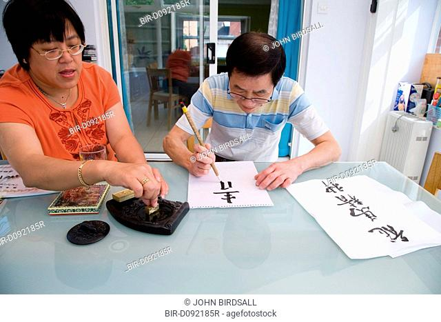Woman mixing ink on a block whilst husband does Chinese art writing