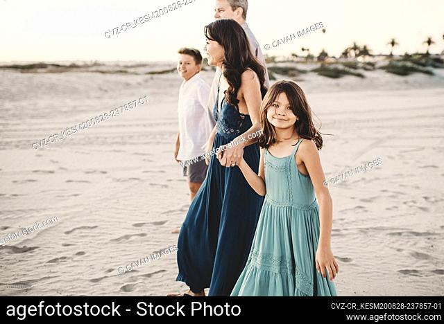 Happy family walking together on the beach holding hands