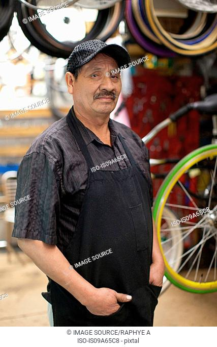 Mechanic standing in bicycle shop