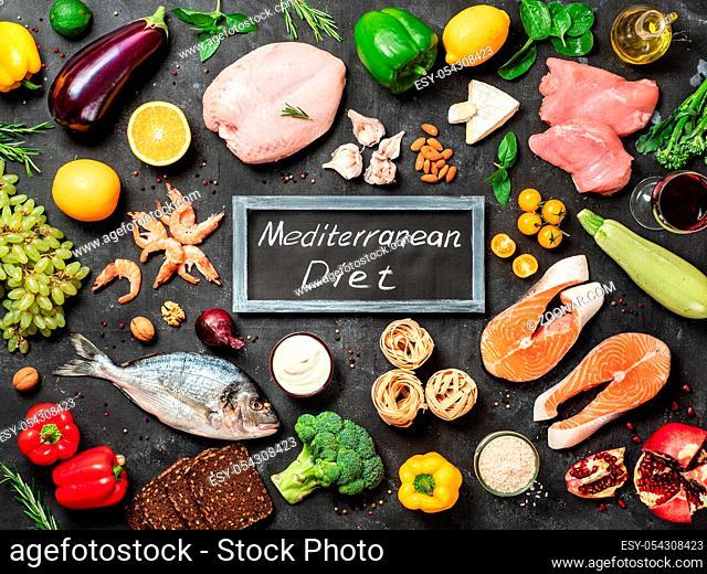Mediterranean diet concept. Top view of food ingredients and chalkboard with words Mediterranean Diet in center. Dark background. Flat lay