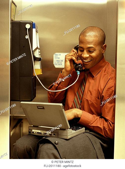 Fv3207, Peter Mintz; Businessman Talking On Payphone, Typing On Laptop