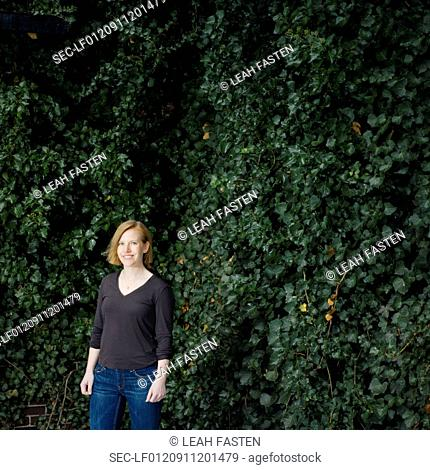 Woman standing against ivy foliage