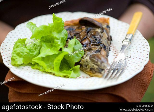 A piece of mushroom tart with lettuce
