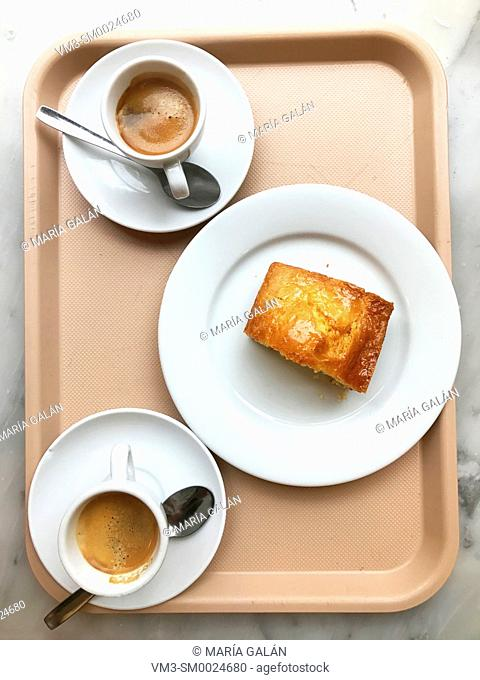 Two cups of coffee and piece of cake on a tray. View from above