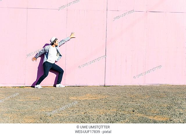 Young man in front of pink construction barrier, feeling trapped