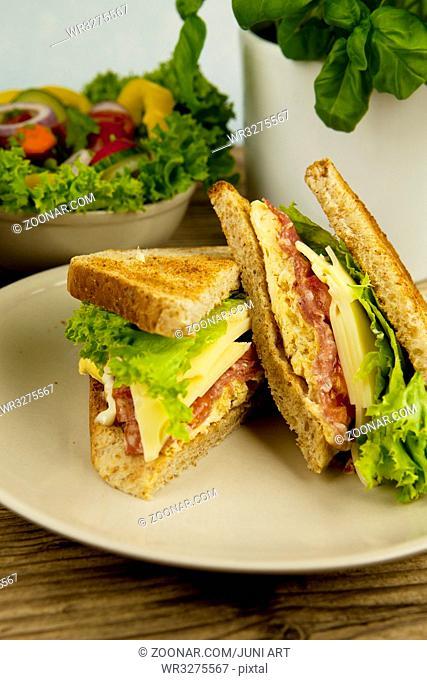 frisches leckeres club Sandwisch mit schinken und Käse auf einem Holzbrett