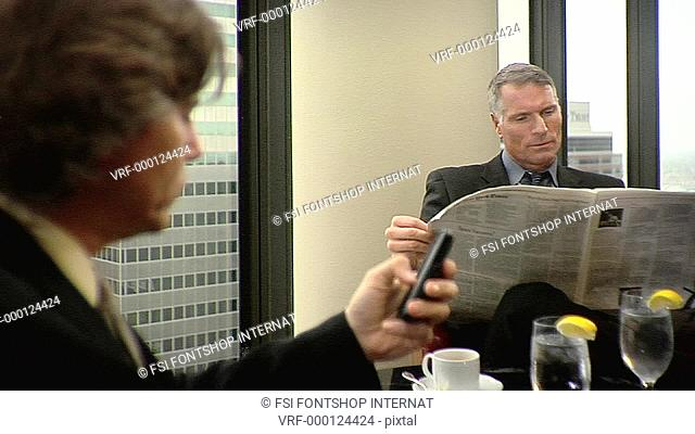 CU, R/F, Diminishing Perspective, A businessman uses a mobile phone while another reads a newspaper