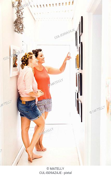 Two female friends, foam rollers in hair, looking at pictures on wall