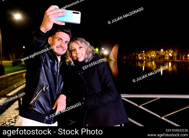Two young friends take a selfie with the mobile in a park