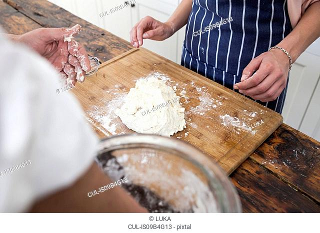 Over shoulder view of hands of two women preparing dough on chopping board
